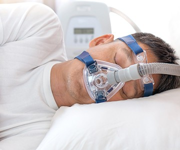 Man sleeping with full CPAP mask