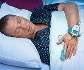 Man sleeping in bed with home sleep test in The Woodlands, TX