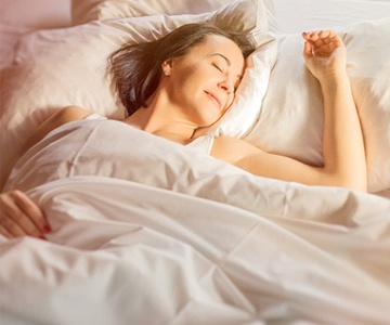 Happy woman sound asleep in bed with white sheets
