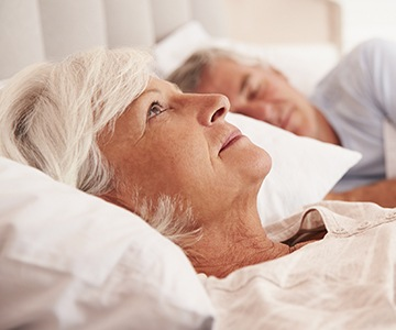 Woman awake next to snoring man