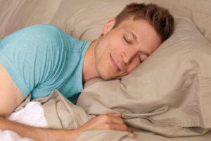 man sleeping peacefully smiling
