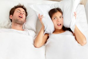 a man snoring and a woman using a pillow to cover her ears