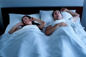 a man snoring and a woman plugging her ears while sleeping