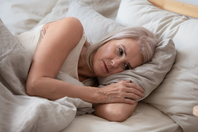 Worried older woman lying awake in her bed
