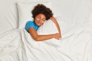Woman with sleep apnea soundly sleeping in white sheets