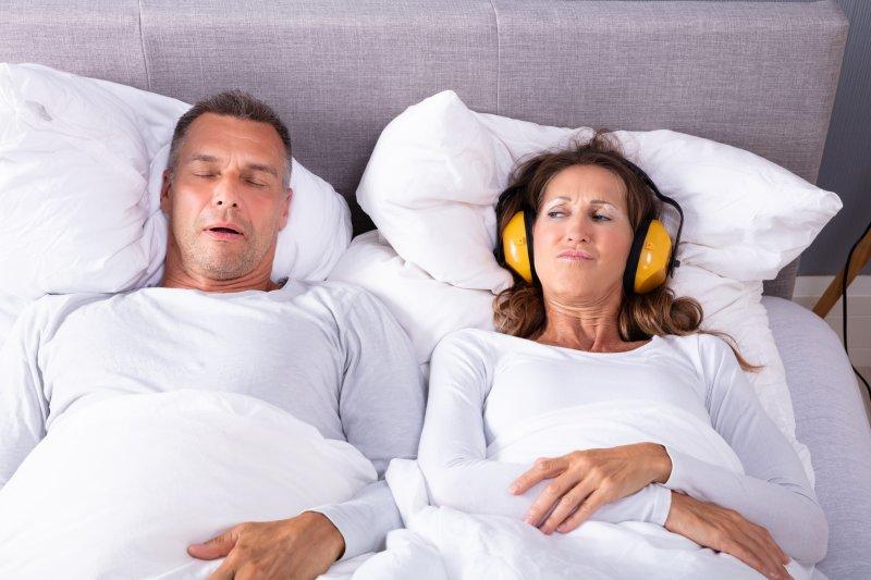 Man with sleep apnea snoring, woman wearing headphones